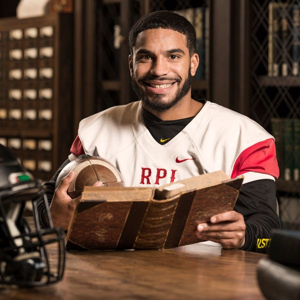 Student football player reading a historical book in the Archives