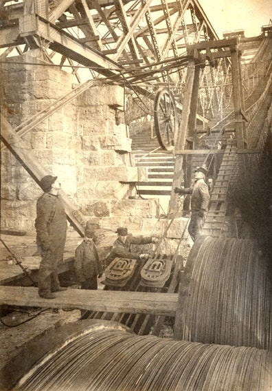 Stringing cable on the Williamsburg Bridge. Othniel Nichols and Leffert Buck in work clothes looking up as cable is strung. Two other men are visible near the cable shoes.