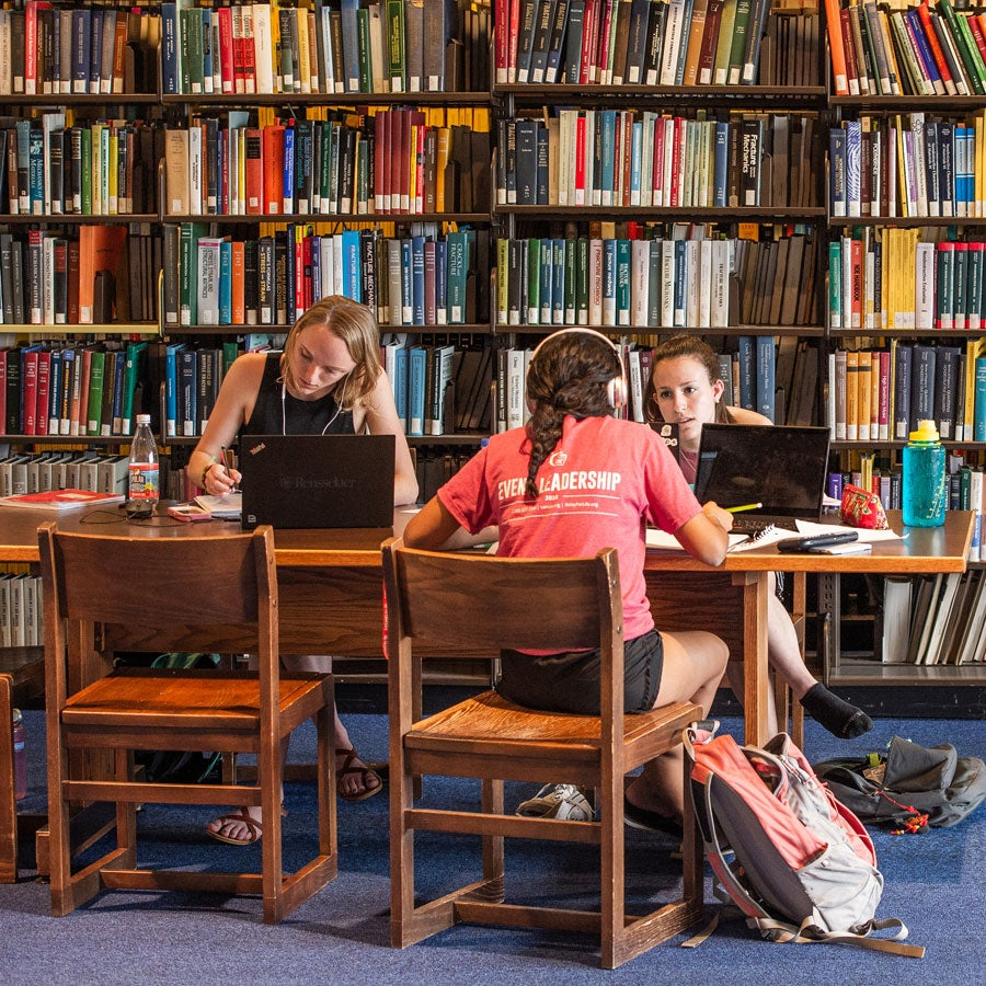 Three students study at a table in front of shelves of library books